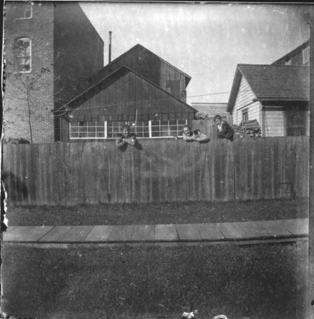 photo of Three Unidentified People Behind Fence