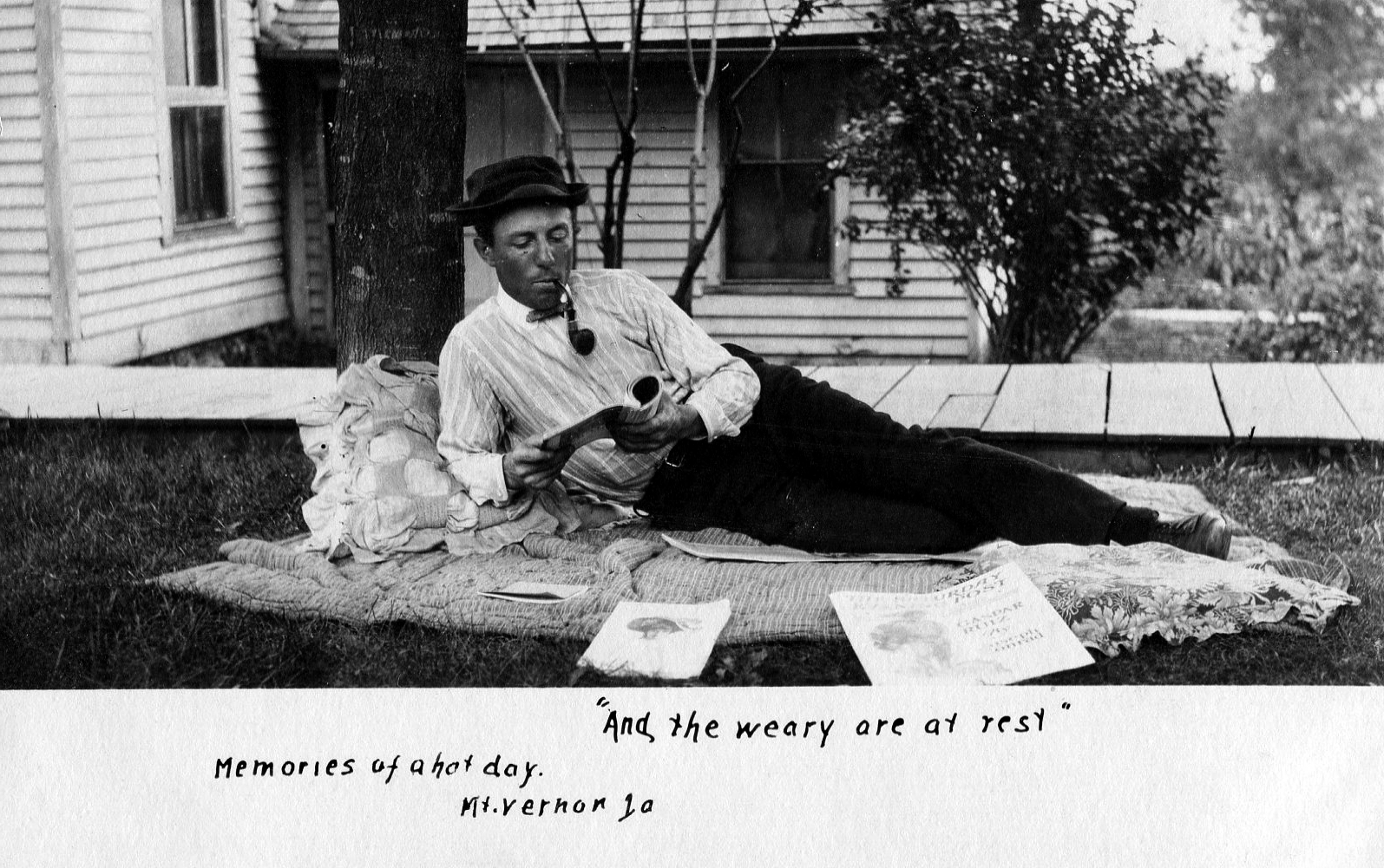 photo of Unidentified Man Lying Down While Reading and Smoking a Pipe