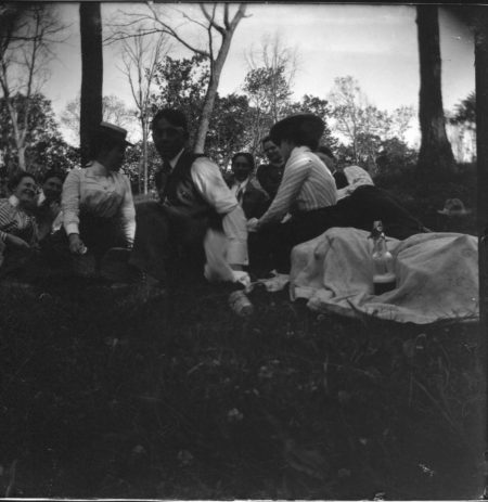 photo of Unidentified Men and Women Sitting at a Picnic