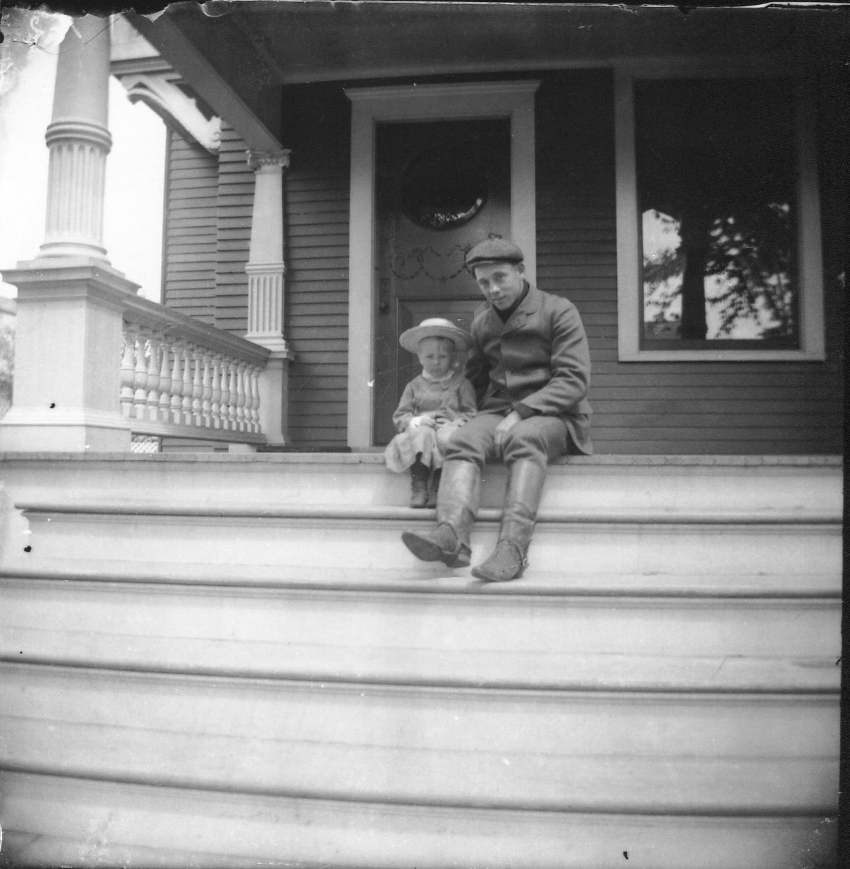 photo of Unidentified Young Man with Little Girl on a Front Porch