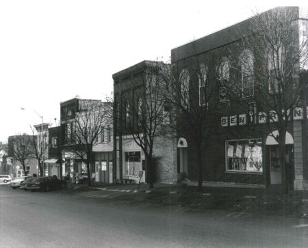 Photo of buildings on South side of First Street W. Photographed 1990 by Barbara Beving Long.
