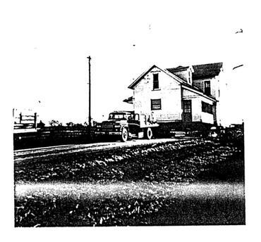 Photo of a truck moving a house